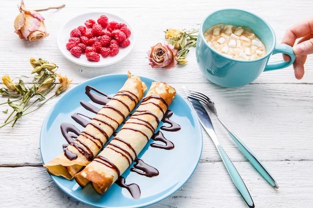 Crêpes faites maison ou blini russe avec une sauce au chocolat sur une plaque sur un fond en bois blanc.