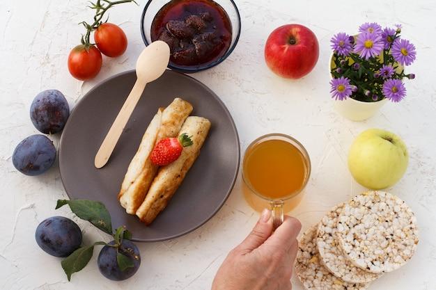 Des crêpes faites maison fourrées de fromage cottage, une fraise dans l'assiette, des prunes, un bol en verre avec de la confiture, une cuillère en bois, des pommes, des gâteaux de riz soufflé, une main de femme avec une tasse de thé. vue de dessus.