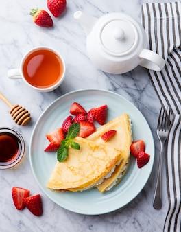 Crêpes, fines crêpes aux fraises fraîches et ricotta, fromage à la crème. vue de dessus.