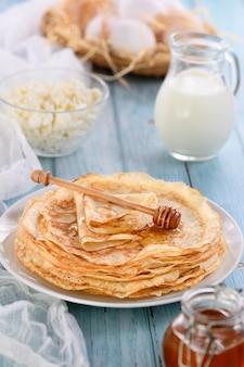 Crêpes fines faites maison avec du miel empilées dans une pile sur une table avec un pot de lait
