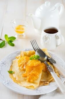 Crêpes fines avec sauce aux agrumes orange pour le petit déjeuner sur une surface légère