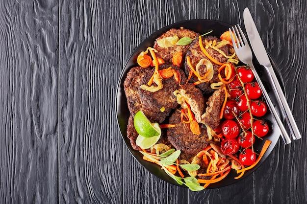 Crêpes de foie de poulet aux carottes, oignons servis sur une plaque noire avec tomates grillées et tranches de citron vert sur une table en bois