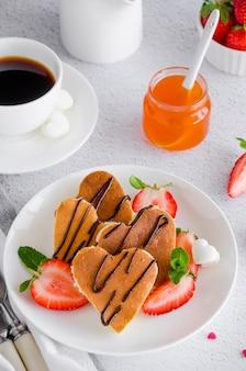 Crêpes en forme de coeur avec sauce au chocolat et fraises fraîches sur une plaque blanche avec une tasse de café