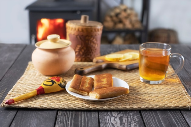 Crêpes fourrées et thé au citron sur une table en bois