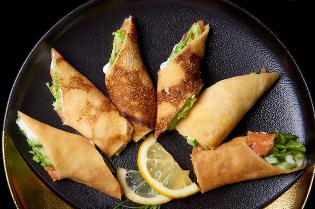 Crêpes fourrées et tranches de citron sur un plat.