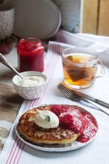 Crêpes à la fraise, crème sure et framboises et tisane sur une table lumineuse