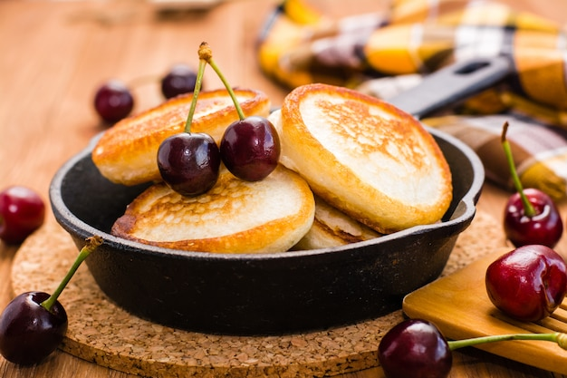 Crêpes frites dans une poêle en fer et des cerises mûres sur une table en bois
