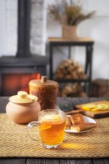 Crêpes avec garniture et thé au miel et citron sur une table en bois dans le contexte d'une cheminée en feu
