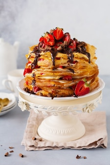Crêpes gâteau aux crêpes avec crème pâtissière, garniture au chocolat et fraises aux baies sur stand vintage.