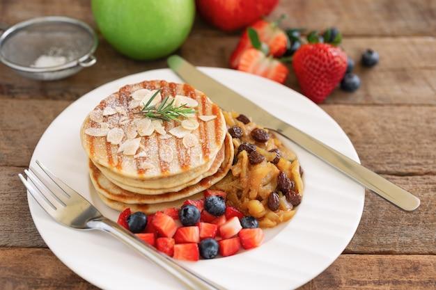Crêpes ou gâteaux chauds faits maison empilés sur une assiette blanche avec des fruits frais et une sauce aux pommes et aux raisins secs sur une table en bois.