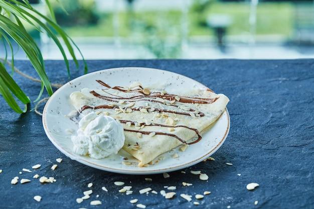 Crêpes à la glace, saupoudrage, chocolat sur la plaque blanche dans la surface sombre