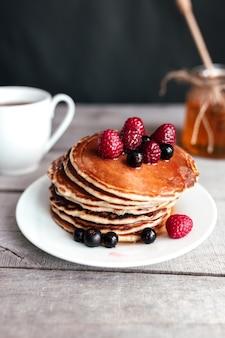 Crêpes juteuses aux baies et miel sur une assiette blanche, cuillère, pot, table en bois, tasse à café.