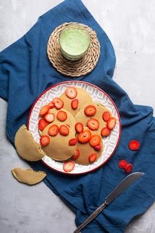 Crêpes maison aux fraises et au beurre. prêt pour le petit déjeuner. latte au matcha sur la table, mise à plat, vue de dessus