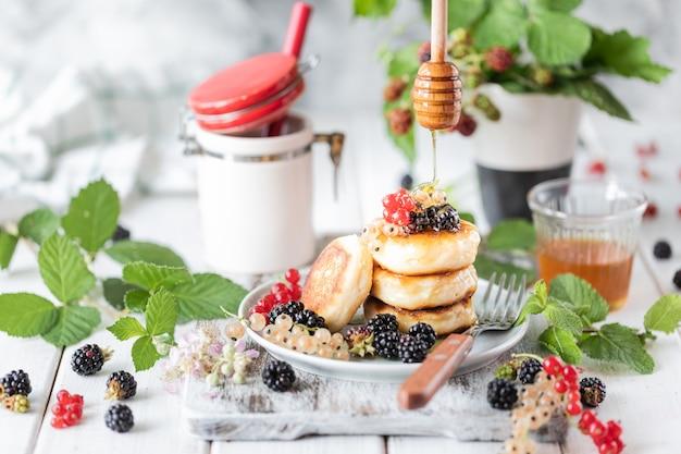 Crêpes maison aux fruits rouges et réveil sur bois blanc