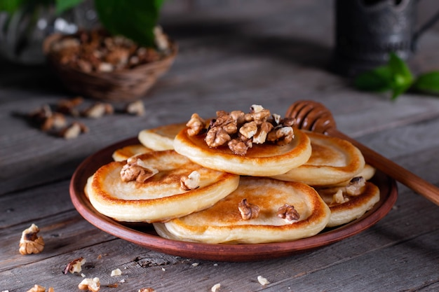 Crêpes maison aux noix et miel dans une assiette en céramique sur une vieille table en bois. petit-déjeuner savoureux et sain