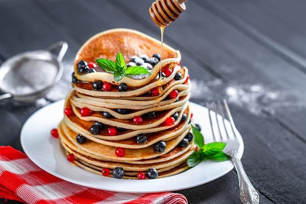 Crêpes maison cuites au four sucrées avec des baies, de la menthe et du sucre en poudre coulant avec du miel pour un délicieux petit déjeuner.