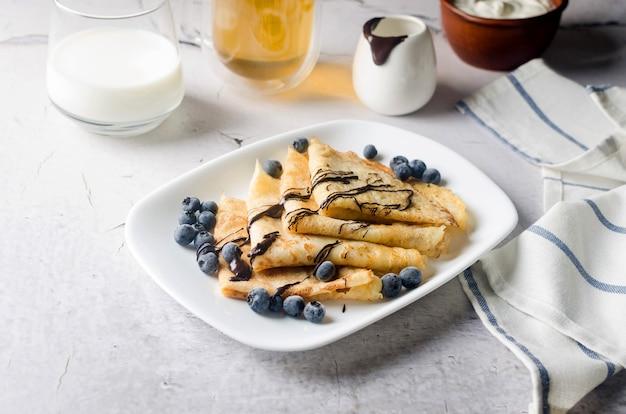 Crêpes maison, délicieuses crêpes fines au chocolat et baies sur une assiette blanche pour le petit-déjeuner avec une tasse de thé. cuisine traditionnelle russe.