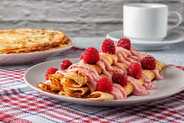 Crêpes maison fraîchement préparées avec des framboises fraîches et du yaourt