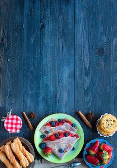 Crêpes maison fraîches servies sur une assiette avec des fraises et des bleuets, sur un fond en bois sombre,