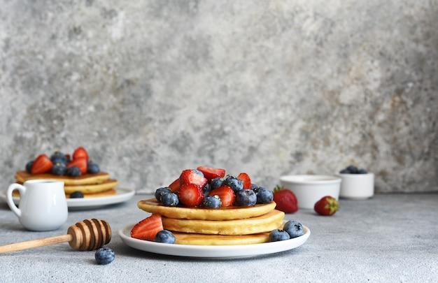 Crêpes maison avec fraises et myrtilles pour le petit déjeuner sur la table de la cuisine.