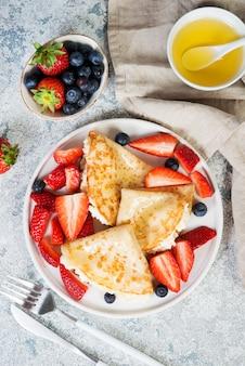 Crêpes minces au ricotta et fraises fraîches sur fond de béton gris.