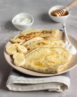 Crêpes minces avec du yaourt naturel, du miel et de la banane sur une assiette