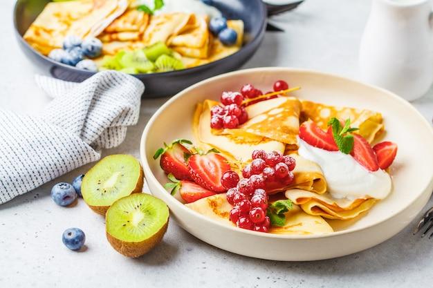 Crêpes minces faites maison et servies avec de la crème de lait caillé, des fruits et des baies en plaques noir et blanc