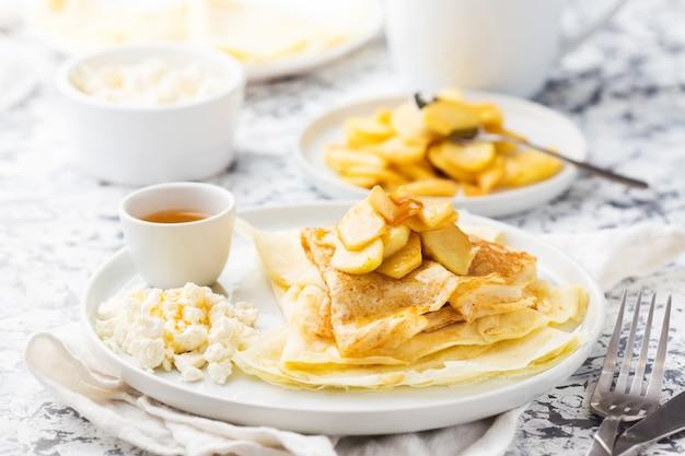 Crêpes minces russes traditionnelles avec pomme, fromage cottage et miel sur une plaque blanche