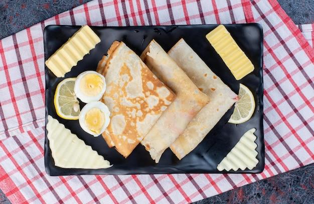 Crêpes avec oeuf, fromage et beurre sur un plateau.