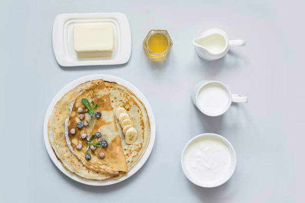 Crêpes, pancakes minces sur une plaque blanche.
