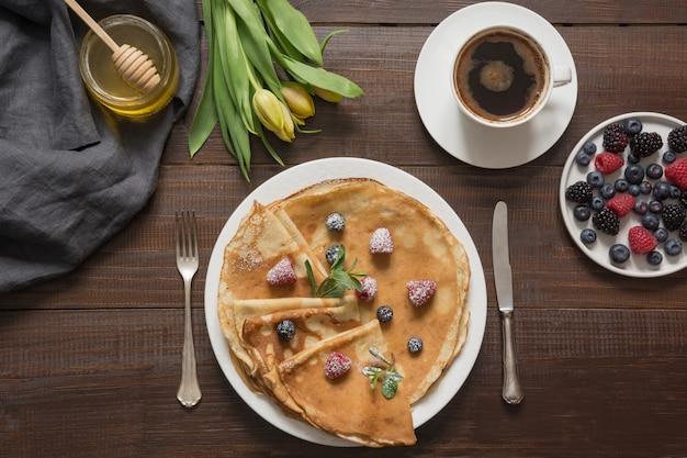Crêpes petit déjeuner russe traditionnel, café, baies, miel. printemps. shrovetide.