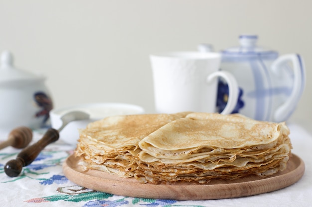 Crêpes de petit déjeuner servies avec de la crème sure et du miel.