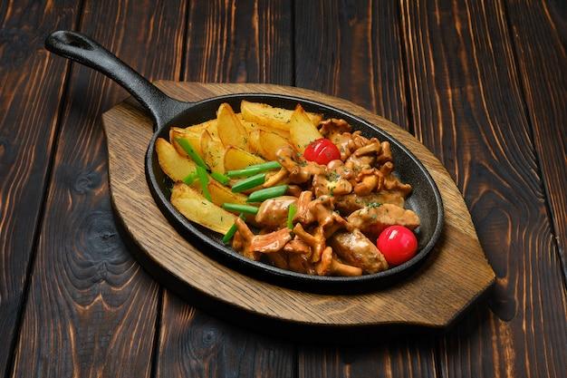 Crêpes de pommes de terre aux girolles et porc dans une poêle en fonte