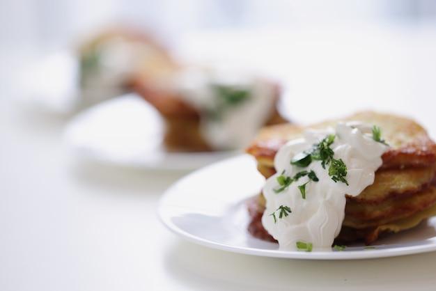 Crêpes de pommes de terre à la crème sure et aux herbes sur une assiette cuisinant un délicieux concept de petit-déjeuner