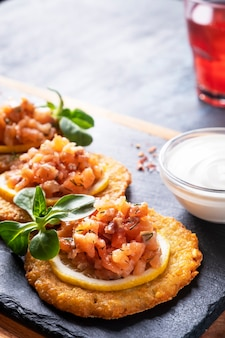 Crêpes de pommes de terre croustillantes au saumon et crème sure. draniki au saumon sur une pierre noire