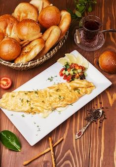Crêpes pour le petit-déjeuner, omelettes avec salade de légumes et petits pains en plaque blanche