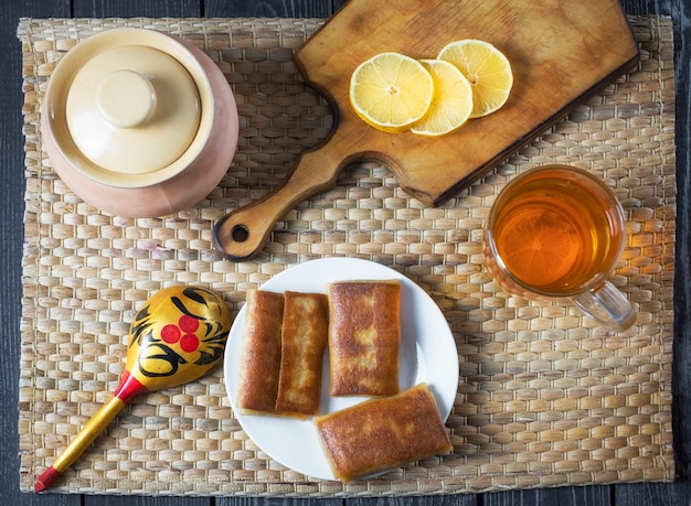 Crêpes remplies et thé au citron pour les vacances maslenitsa dans un style rustique russe
