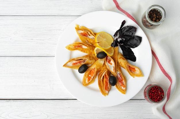 Crêpes russes farcies au saumon salé sur la surface de la table en bois blanc