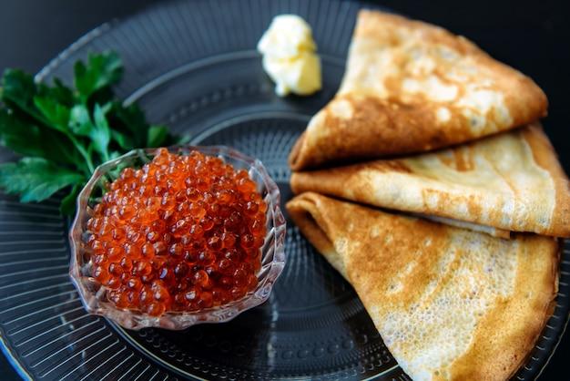 Crêpes russes minces traditionnelles avec caviar rouge, beurre et légumes verts