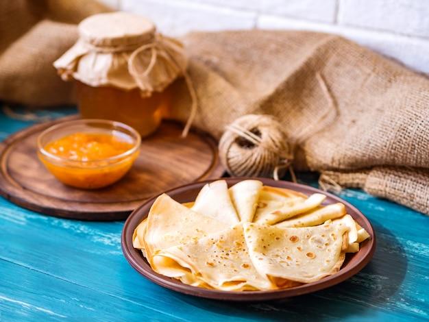 Crêpes russes sur une plaque de bois sur une table d'azur avec du miel et de la confiture d'abricot.