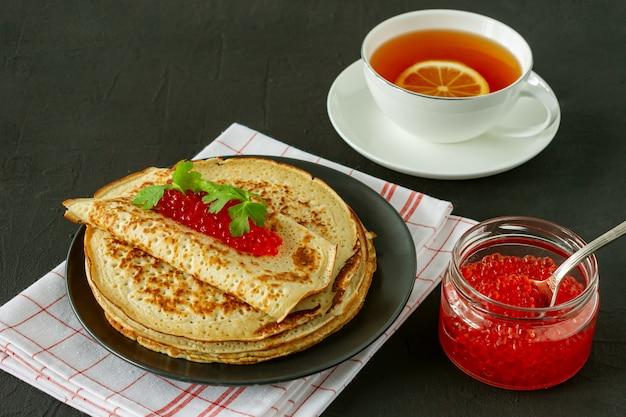 Crêpes russes traditionnelles blini empilées dans une assiette avec du caviar rouge et du thé au citron chaud sur fond de bois. repas traditionnel du festival russe maslenitsa. cuisine russe, cuisine russe.