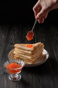 Des crêpes russes traditionnelles avec du caviar rouge avec une cuillerée à thé d'argent sont disposées sur une pile de crêpes.