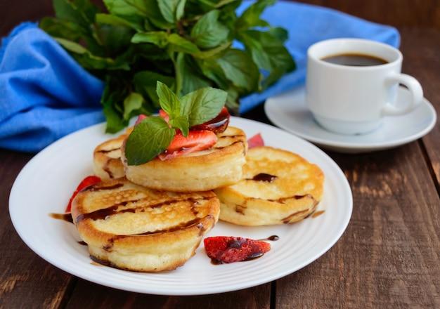 Crêpes rustiques avec des fraises fraîches et du chocolat sur une plaque blanche et une tasse de café