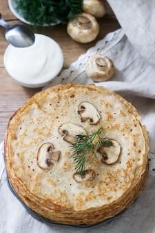 Crêpes de sarrasin servies avec de la crème sure et de l'aneth sur une table en bois. style rustique.