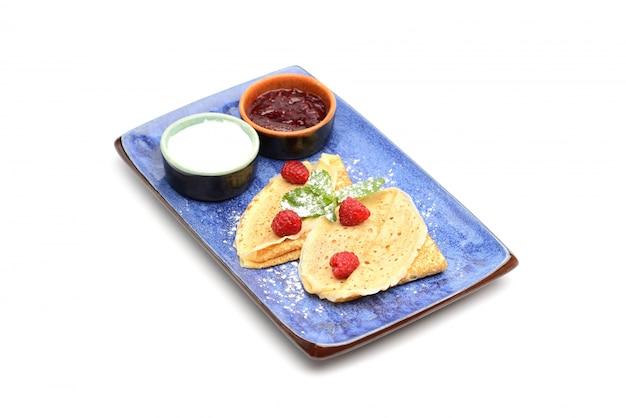 Crêpes à la sauce aux baies et à la crème sure, décorées de framboises et de menthe.