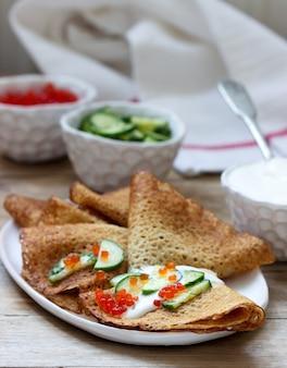 Crêpes de seigle et de grains entiers servies avec de la crème sure, du caviar et des concombres. style rustique.