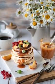 Crêpes de semoule de maïs au caramel salé servi avec des baies et des fruits sur un fond en bois blanc.