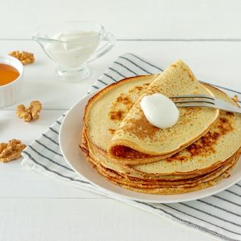Crêpes servies avec du sirop de miel et de la crème sure sur une assiette blanche. crêpes traditionnelles pour la semaine des crêpes ou le mardi gras.