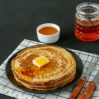 Crêpes servies avec du sirop de miel et du beurre sur une assiette noire. crêpes traditionnelles pour la semaine des crêpes ou le mardi gras.