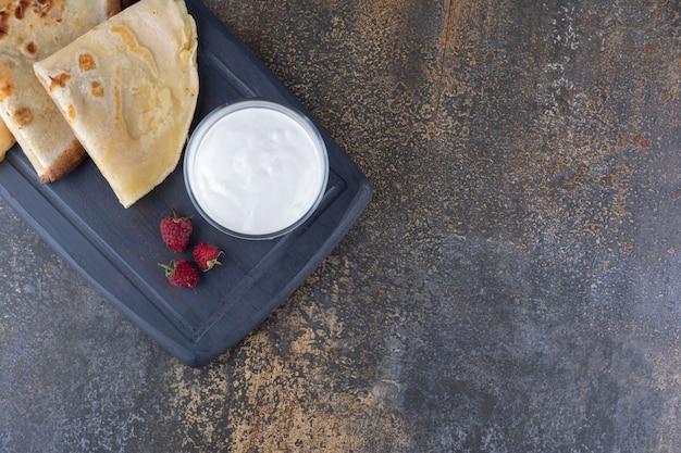 Crêpes servies avec des framboises et une tasse de crème sure